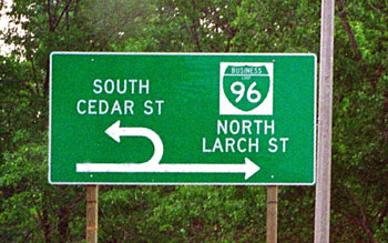 Figure 87. Example of median U-turn signing in Michigan. Photo. The picture shows a direction sign in advance of a U-turn location. The through arrow points north to Business 96 (Larch Street). The U-turn arrow points south to Cedar Street.
